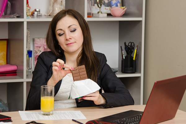 Woman eating chocolate bar at her desk.