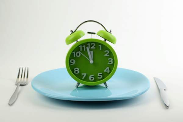 Dinner plate with alarm clock on it.