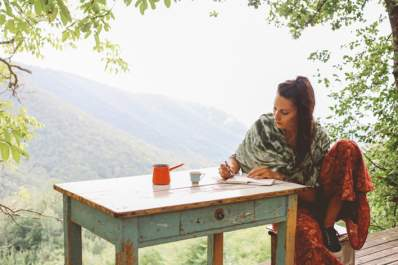 Woman writing a letter at desk outside.