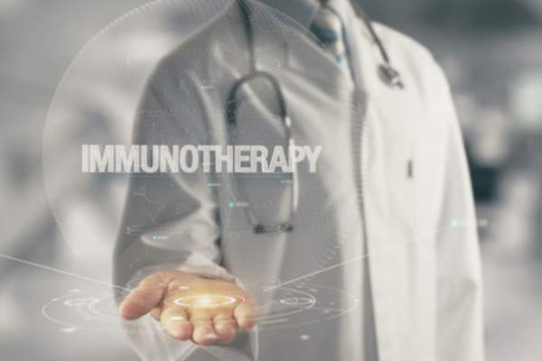 Doctor holding out hand with digital immunotherapy image.