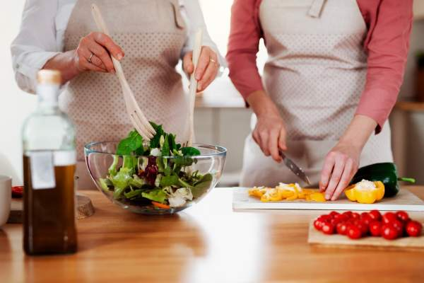 two woman in kitchen making big salad