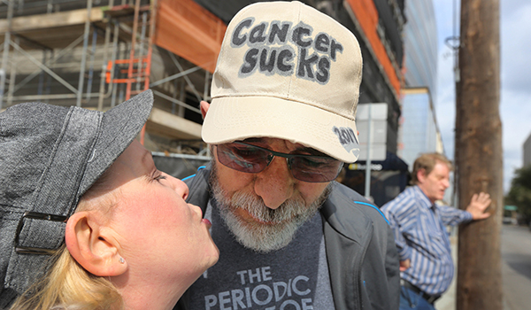 "Jeffrey Weiss wears a hat that says ""Cancer Sucks"" as his wife kisses him"