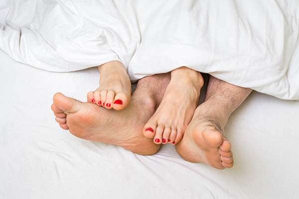 Feet of couple under covers in bed.