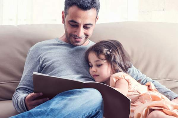 Father reading book to young daughter on couch.