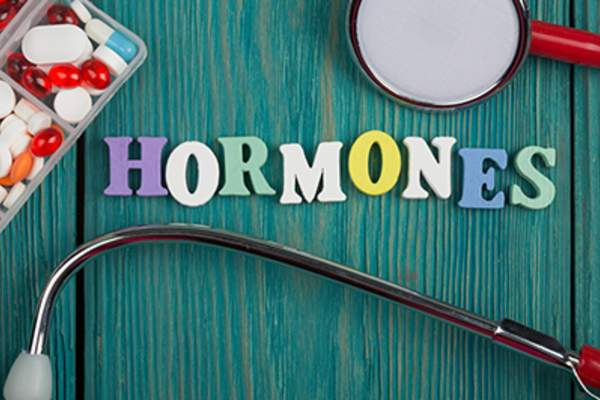Text 'Hormones' of colored wooden letters, stethoscope and pills