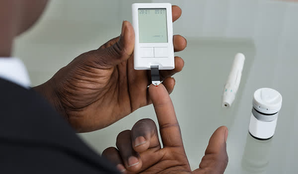 Man measuring his blood sugar with a glucose meter.