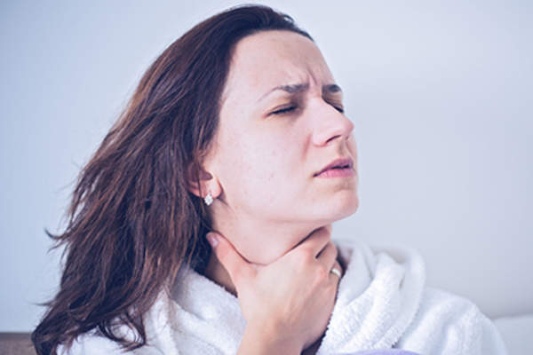Woman with throat swelling as a side effect of chronic hives medication.