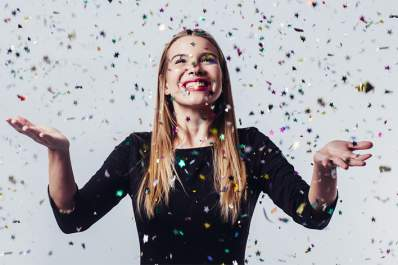 Happy young woman celebrating with confetti.