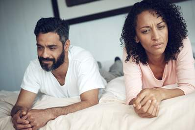 Unhappy couple lying in bed.