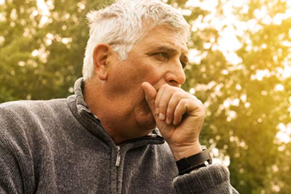 Adult man coughing outdoors.