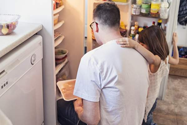 Father holding daughter getting food out of fridge.