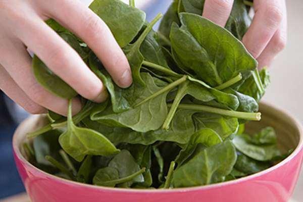 Tossing spinach in a bowl.