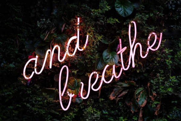 "Neon sign reading ""and breathe"""