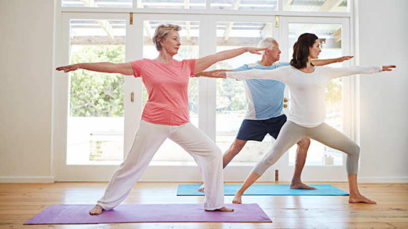 Older couple working with yoga instructor