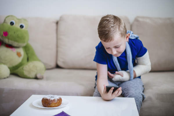 Boy with broken arm with mobile phone