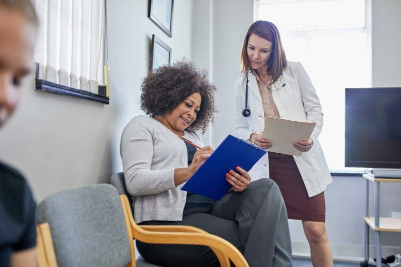 Female doctor and patient discussing paperwork in clinic waiting room