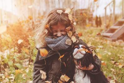 Girl playing in autumn leaves with her dog, face covered with scarf.