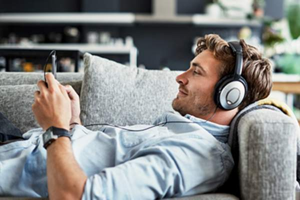 Man relaxing and listening to music on a couch.