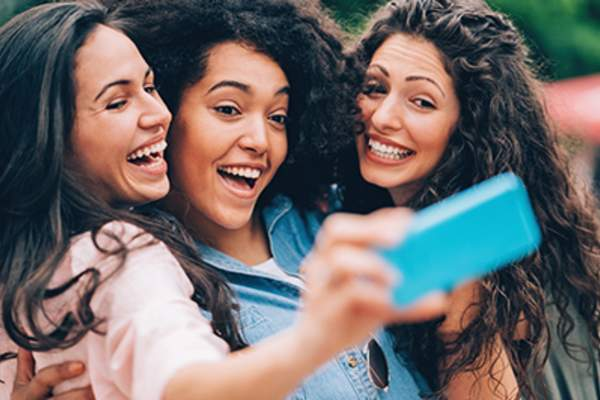 Laughing friends posing for a selfie.