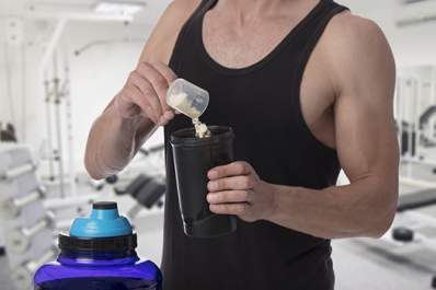 Man adding protein powder to shaker at gym.