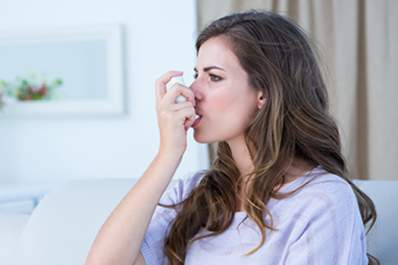 young woman using inhaler image