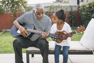 Grandfather and granddaughter playing guitars together.