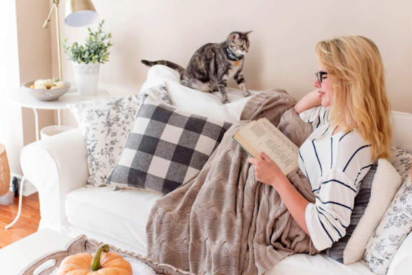 woman under blanket reading on couch with cat