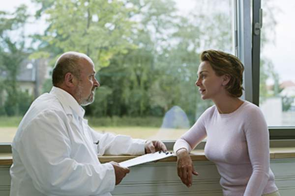 Woman talking to her doctor by a window.