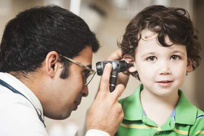 Doctor checking a toddler's ears.