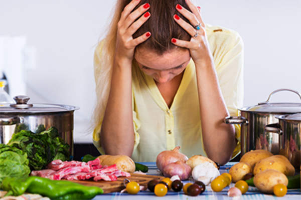 Woman with headache, food on counter.