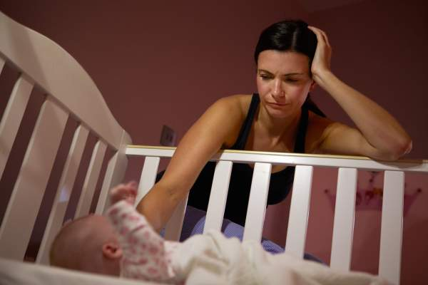Tired mother with baby in crib.