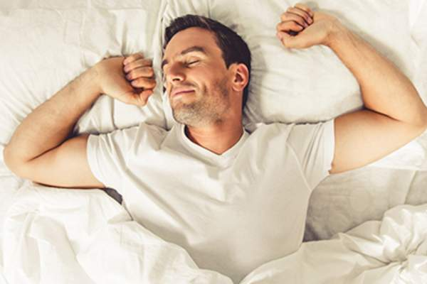 Well-rested man waking up in bed image.