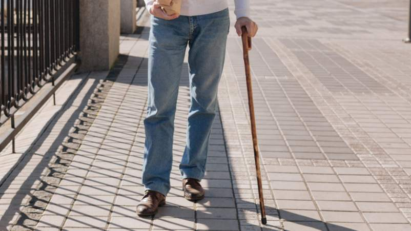 Man walking with a cane in the park.