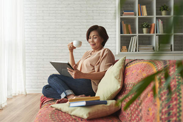 Woman relaxing on couch at home, reading and drinking tea.