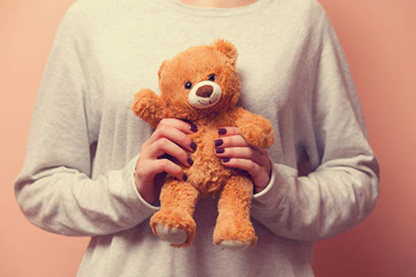 Woman cuddling a teddy bear for comfort.