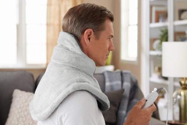 Man using Renue® Neck Wrap, made by Sunbeam®