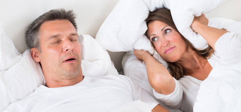 man snoring annoying woman