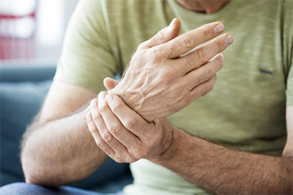 Senior man holding wrist with hand pain.