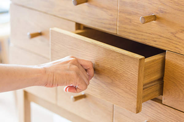 Woman opening a wooden drawer.