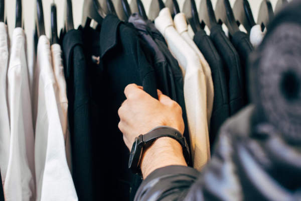 man looking through rack of jackets