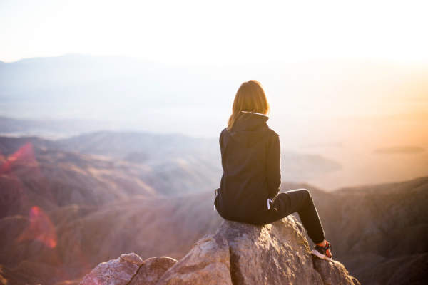 woman sitting on mountain looking at sunset