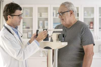 Doctor weighing a senior man.