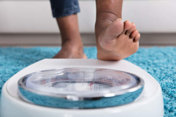 Stepping on scale obesity concept.