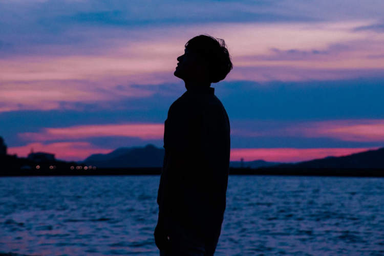 silhouette of man at sunset looking into distance