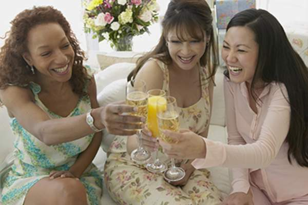 Three smiling women raising champagne flutes, one with orange juice.