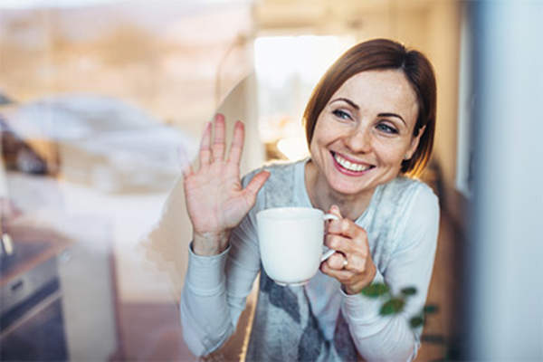 Smiling woman at window saying good-bye with cup of coffee.