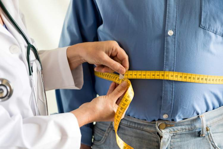 Doctor measuring waist of overweight man.