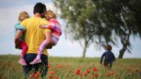 Man walking through the flowers with his children