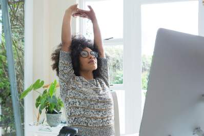 Woman stretching while working at her desk and laptop.