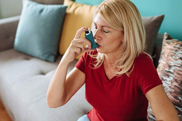 Asthmatic woman using an inhaler.